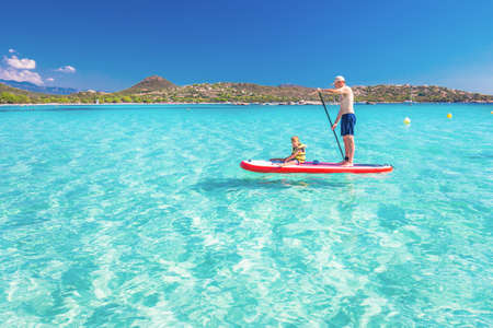 Father with his little happy son having fun on stand up paddle board on Corsica island, France.