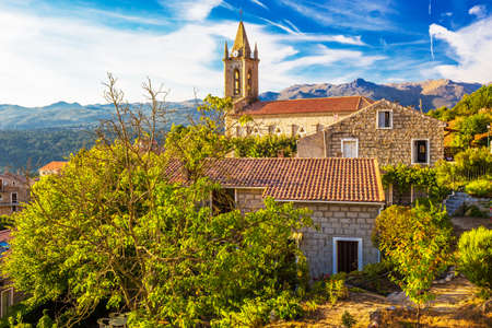 Church in Zonza village with typical stone houses during sunset, Corsica island, France, Europe. Zonza is located in the mountain chain of Barocagio-Marghese which extends to the south of the Incudine massif. Stock Photo
