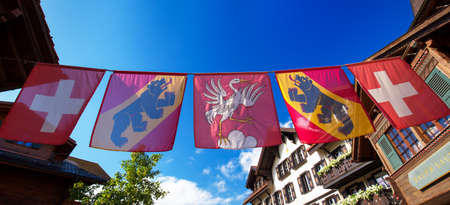 canton berne: Swiss flag in old city center of Gstaad town, famous ski resort in canton Bern, Switzerland.