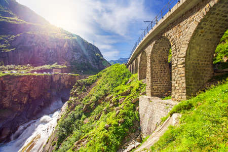 singularity: River Reuss flowing through the railroad bridge Teufelsbruecke - Devils bridge.The Schollenen Gorge is a gorge formed by the upper Reuss in the Swiss canton of Uri between the towns of Goschenen and Andermatt. It provides access to the St Gotthard Pass. Stock Photo