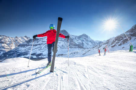 piste: Young attractive caucasian skier with ski on ski slope in famous Jungfrau ski resort, Grindelwald, Switzerland