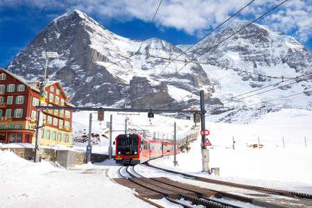 KLEINE SCHEIDEGG, SWITZERLAND - January 2017 - Famous train (Jungfrau railway) goes to Alpine mountain resort with famous Eiger, Monch and Jungfrau mountain, Grindelwald, Berner Oberland, Switzerland. Stock Photo - 75216033