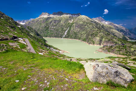 Panoramic mountain road leading to Grimselpass with Grimselsee, totensee and Swiss Alps in the background.