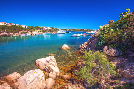 Red rocks in harbor with tourquise clear water at Porto Cervo town. Porto Cervo is capital of Costa Smeralda, Sardinia, Italy.