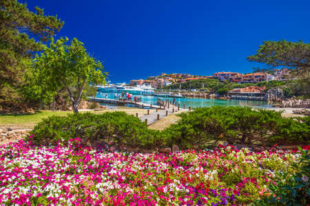 Coastline promenade with pine trees and tourquise clear water at Porto Cervo town. Porto Cervo is capital of Costa Smeralda, Sardinia, Italy. Stock Photo