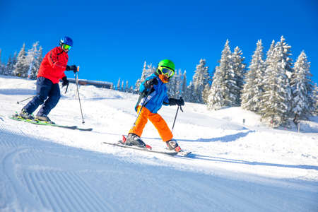 Happy little boy skiing with his father on ski holiday in Alps.