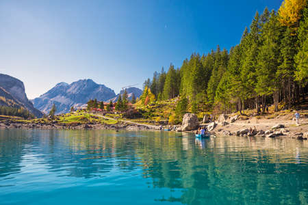 OESCHINENSEE, SWITZERLAND - October 2017 - Amazing tourquise Oeschinnensee with waterfalls, wooden chalet and Swiss Alps, Berner Oberland, Switzerland.