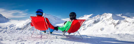Young couple sitting on deck chairs and enjoying stunning view of Alps, Europe.