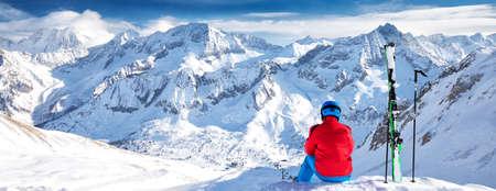 Junger glücklicher Skifahrer, der auf der Spitze der Berge sitzt und Blick auf Rhätische Alpen, Tonale-Pass, Italien, Europa genießt.