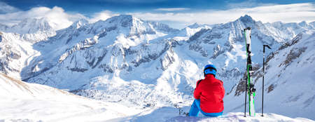 Young happy skier sitting on the top of mountains and enjoying view of Rhaetian Alps, Tonale pass, Italy, Europe. Archivio Fotografico