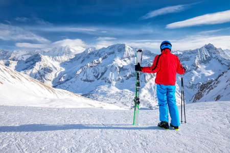 Young happy skier sitting on the top of mountains and enjoying view of Rhaetian Alps, Tonale pass, Italy, Europe.