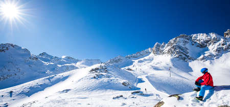 Young happy skier sitting on the top of mountains and enjoying view of Rhaetian Alps, Tonale pass, Italy, Europe. Stock Photo