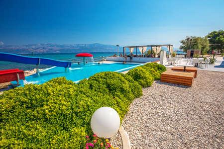 BRAC, CROATIA - August 6, 2018 - Seaside promenade on Brac island with palm trees and turquoise clear ocean water, Supetar, Brac, Croatia Editorial
