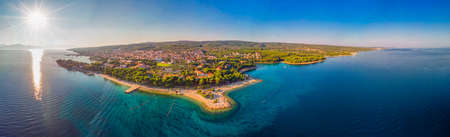 Aerial view of seaside promenade in Supetar town on Brac island with palm trees and turquoise clear ocean water, Supetar, Brac, Croatia, Europe.