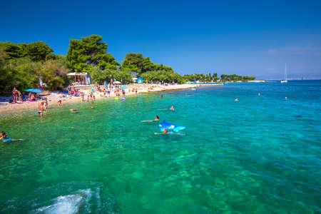 BRAC, CROATIA - August 6, 2018 -Pebble beach on Brac island with turquoise clear ocean water, Supetar, Brac, Croatia Editorial