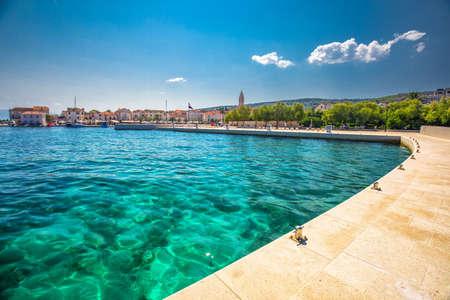 Seaside promenade in Supetar town on Brac island with palm trees and turquoise clear ocean water, Supetar, Brac, Croatia, Europe.