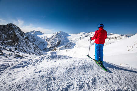 Young happy attractive skier on the top of mountains enjoying the view from Presena Glacier, Tonale, Italy. 写真素材