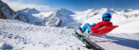 Junge, glückliche, attraktive Skifahrerin, die auf den Bergen sitzt und die Aussicht vom Presena-Gletscher, Tonale, Italien genießt.