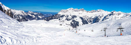 Beautiful winter landscape with Swiss Alps. Skiers skiing in famous Engelgerg - Titlis ski resort, Switzerland, Europe.  Stock Photo