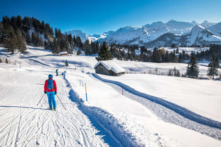 Beautiful winter landscape. People skiing in Mythenregion ski resort, Ibergeregg, Switzerland, Europe