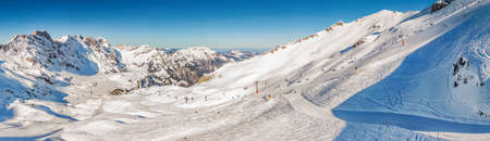 Beautiful winter landscape with Swiss Alps. Skiers skiing in famous Engelgerg - Titlis ski resort, Switzerland, Europe.