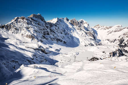 Beautiful winter landscape with Swiss Alps. Skiers skiing in famous Engelgerg - Titlis ski resort, Switzerland, Europe. Stock Photo - 121475949