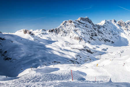 Beautiful winter landscape with Swiss Alps. Skiers skiing in famous Engelgerg - Titlis ski resort, Switzerland, Europe. Banque d'images - 121475952