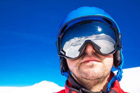 Skieir mit Skibrille und seine Reflexion der Alpenberge Standard-Bild