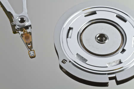 read write head in hard disk drive with platterand spindle in close up shot photo
