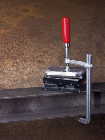 vise grip: hard disks and clamp in rusty background with copy space