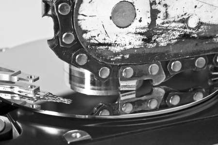 data loss: Chain saw over open hard disk drive. symbol for data loss Stock Photo