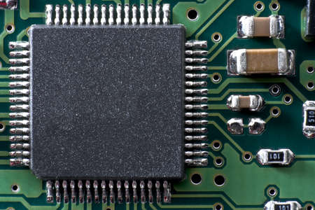 green circuit board with IC and other electronic components. Space for text on IC.