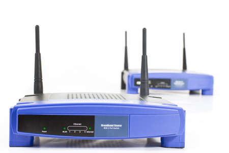 blue internet routers with two antennas. Isolated on white. One in background Stock Photo