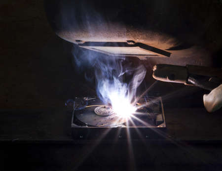 electrode: welding on a hard drive with a electrode. Nice light at the welding shield Stock Photo