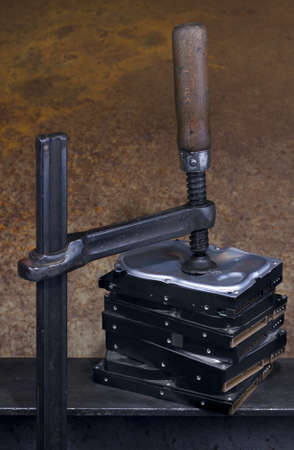 clamp pressing on stack of hard drives. The top drive is deformed Stock Photo - 10079352