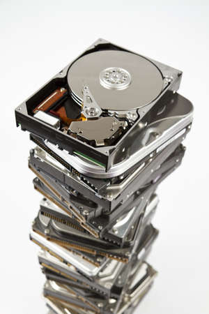 Stack of many different hard drives with opened drives on top. Grey background Imagens