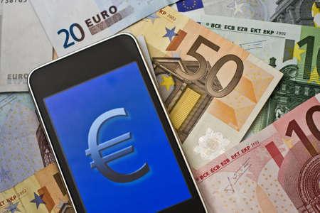 euro symbol on handheld laying on euro banknotes Stock Photo - 10079602