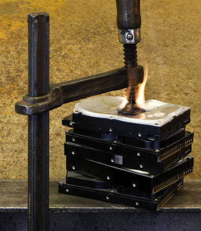 clamp pressing on a stack of hard drives with fire. The top drive is deformed Stock Photo - 10079526
