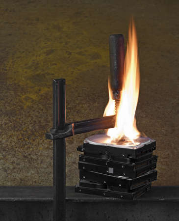 vise grip: flames on stack of pressed hard drives. pressed by clamp Stock Photo