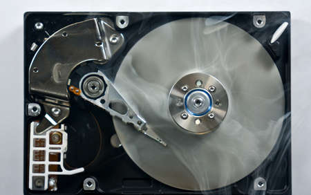 Defect hard disk drive with smoke. Open drive as symbol for data loss. photo