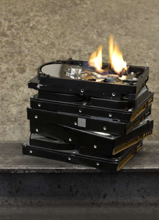 stack of hard drives with top one open and burning.  Stock Photo - 10079542
