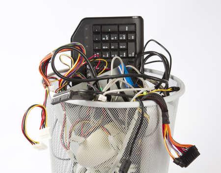 differernt Teile von Computern im Mülleimer. Theres eine Maus, eine Tastatur, eine Stromversorgungsleitungen und viele Kabel
