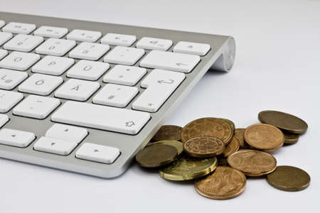 Computer keyboard with white keys and coins Stock Photo - 10079280