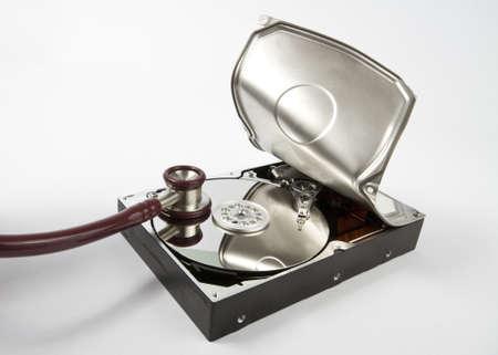 brute: Il disco rigido � aperto con la forza bruta e uno stetoscopio � in ascolto per i dati. Neutral sfondo grigio Archivio Fotografico