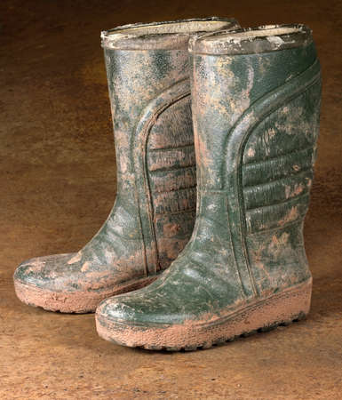 green dirty rubber boots on rusty background Stock Photo - 10079644
