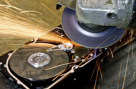 angular grinder producing many sparks when cleaning data from hard disk drive. photo
