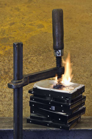 vise grip: burning stack of hard drive pressed together with clamp in rusty background