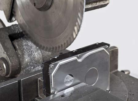 fixed disk: deviding ha hard drive with a circular saw. Neutral backgound