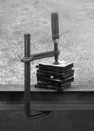 fixed disk: compressed stack of hard disks by clamp. black and white shot Stock Photo