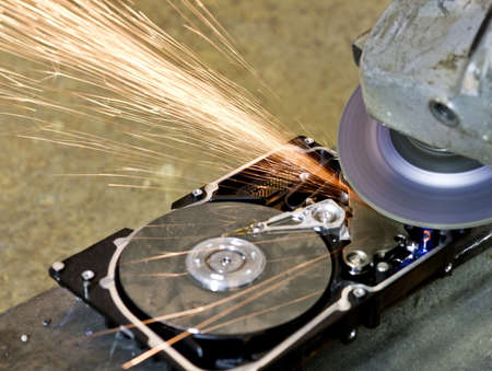 grinder working on open hard drive. Many sparks are flying away. rusty background Stock Photo - 10079282